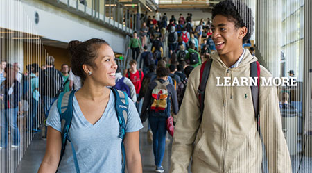 Two students walking with a crowd of fellow students on the stairs behind them and text: Learn More