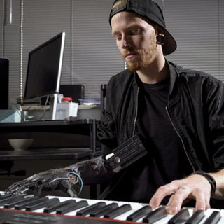 Jason Barnes plays the piano with a new prosthesis that is driven by ultrasound.